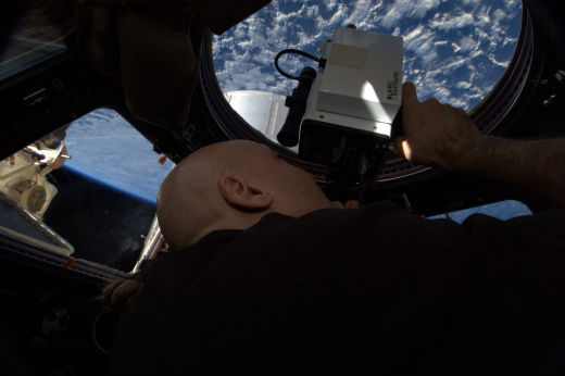 Luca spends some of his free time using a laser tool on the ISS. Credits: ESA/NASA