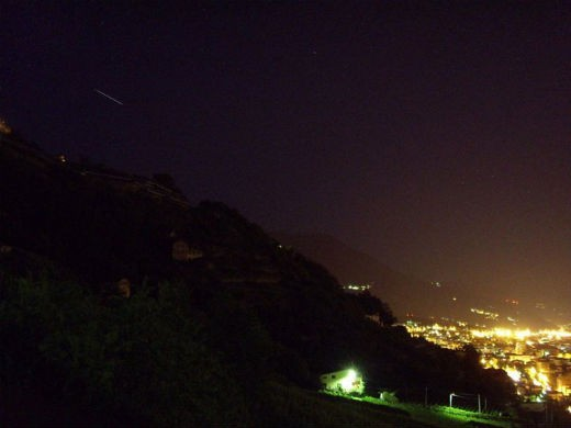 """Picture taken at 20.57z in Aosta, north-western Italy (45°44′14″N 7°19′14″E). ISS comes from the upper-left side, while the city quietly moves to the end of the day. Standard pocket camera, with 8 seconds exposure."" - Chris"